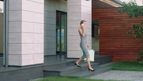 Affärskvinna som går ner trappa från modern byggnad med shoppingpåsar lager videofilmer