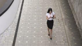 Affärskvinna som går och använder en smart telefon stock video