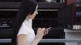 Affärskvinna som går och använder en smart telefon lager videofilmer