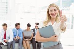 Affärskvinna som gör en gest tummar upp mot väntande på intervju för folk Arkivbild