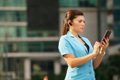 Affärskvinna som gör en påringning med bluetoothapparaten Royaltyfri Bild