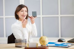 affärskvinna som gör makeup på kontoret royaltyfri foto