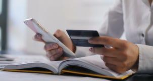 Affärskvinna som gör online-bankrörelsen med kreditkorten, danande en betalning eller investering på internet som skriver in henn lager videofilmer