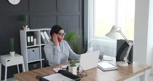 Affärskvinna som gör skrivbordsarbete och talar på mobil lager videofilmer