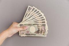 Affärskvinna som ger pengar och pengar för japansk yen för innehav 10.000 i hand på grå väggbakgrund, japansk yen Royaltyfri Foto