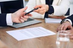 Affärskvinna som ger pennan till affärsmannen som är klar att underteckna avtalet Framgångkommunikation på mötet eller förhandlin Arkivbilder