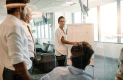 Affärskvinna som ger presentation till kollegor som använder flipbrädet royaltyfri foto