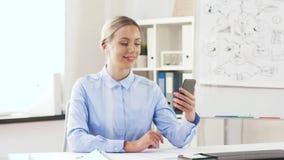 Affärskvinna som har den videopd appellen på cellen på kontoret lager videofilmer