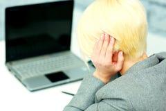Affärskvinna som har en huvudvärk på hennes arbetsplats Arkivbild