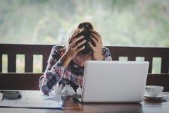 Affärskvinna som har huvudvärk, medan arbeta genom att använda bärbara datorn Comput royaltyfria foton