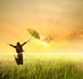 Affärskvinna som hoppar till solnedgången med det röda paraplyet Arkivbild