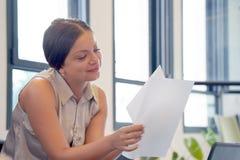 Affärskvinna som i regeringsställning läser en workspace för dokument arkivfoton