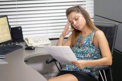 Affärskvinna som i regeringsställning läser en workspace för dokument arkivbilder