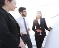 Affärskvinna som i regeringsställning pekar markören till flipboarden på presentation Fotografering för Bildbyråer