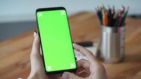 Affärskvinna som i regeringsställning ser mobiltelefonen med den gröna skärmen