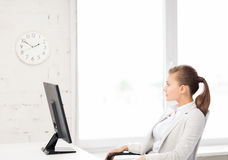 Affärskvinna som i regeringsställning ser väggklockan royaltyfri fotografi