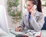 Affärskvinna som i regeringsställning talar på telefonen och arbetar på komp Arkivbild