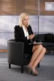 Affärskvinna som i regeringsställning väntar lobbyen Arkivfoton