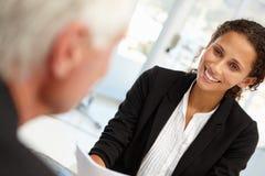 Affärskvinna som intervjuar male anställd Royaltyfri Bild