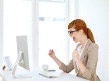 Affärskvinna som jublas i hennes kontor Arkivbild