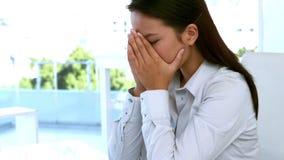 Affärskvinna som känner sig stressad på hennes skrivbord lager videofilmer