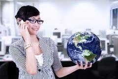 Affärskvinna som kallar och rymmer världsjordklotet Royaltyfri Fotografi