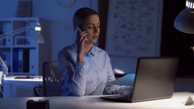 Affärskvinna som kallar på smartphonen på det mörka kontoret arkivfilmer