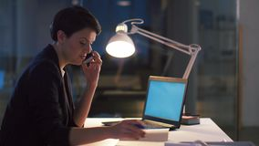 Affärskvinna som kallar på smartphonen på det mörka kontoret stock video