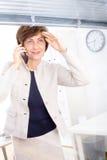 affärskvinna som kallar telefonpensionären Arkivfoton