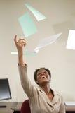 Affärskvinna som kastar skrivbordsarbete i luften Royaltyfri Foto
