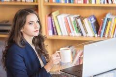 Affärskvinna som koncentrerar och tar ett kaffeavbrott arkivbilder