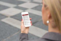Affärskvinna som kontrollerar emailen på smartphonen Arkivbild