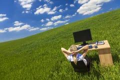 Affärskvinna som kopplar av på skrivbordet i grönt fältkontor Arkivbild