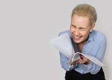 Affärskvinna som läser ett dokument och skratt Fotografering för Bildbyråer