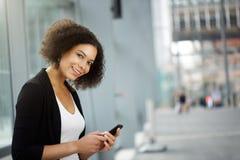 Affärskvinna som ler med mobiltelefonen Arkivfoto