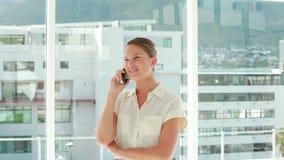 Affärskvinna som ler, medan ringa lager videofilmer