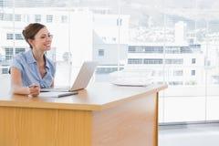 Affärskvinna som ler på hennes skrivbord Arkivfoto