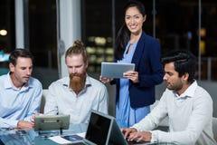 Affärskvinna som ler på kameran medan kollegor som diskuterar över den digitala minnestavlan och bärbara datorn arkivfoto