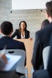 Affärskvinna som levererar presentation på konferensen royaltyfri fotografi