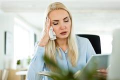 Affärskvinna som lider influensa och feber på arbete royaltyfri fotografi