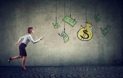 Affärskvinna som motiveras av pengar som hänger på en fiska krok Affärskvinnaspring för kassadollar royaltyfri foto