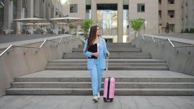 Affärskvinna som ner kommer trappan från affärscentrum med resväskan stock video