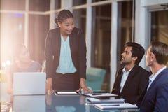 Affärskvinna som påverkar varandra med coworkers i ett möte i konferensrummet royaltyfri fotografi