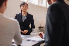 Affärskvinna som påverkar varandra med kollegor under presentation royaltyfri foto