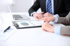 Affärskvinna som pekar in i finansiellt diagram och talar med hennes manliga partner, slut upp av händer Arkivbilder