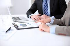 Affärskvinna som pekar in i finansiellt diagram och talar med hennes manliga partner, slut upp av händer Arkivbild