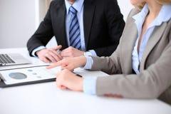 Affärskvinna som pekar in i finansiellt diagram och talar med hennes manliga partner, slut upp av händer Royaltyfri Fotografi