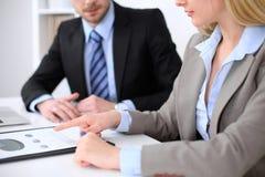 Affärskvinna som pekar in i finansiellt diagram och talar med hennes manliga partner, slut upp av händer Fotografering för Bildbyråer