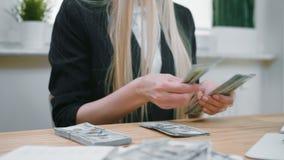 Affärskvinna som in räknar händer för kassa Kantjustera sikten av kvinnlign, i elegant dräktsammanträde på träskrivbordet och att arkivfilmer