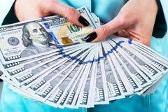Affärskvinna som räknar pengar i händer Handfullpengar Erbjudande pengar Händer för kvinna` s rymmer pengarvalörer av 100 dollar Fotografering för Bildbyråer